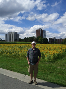"Pete at Farm with Civic in Background.jpg"" with Caption: ""Pete Anderson posing near the threatened experimental plots with the Civic Hospital in the background. Photo credit: Laura Cameron."