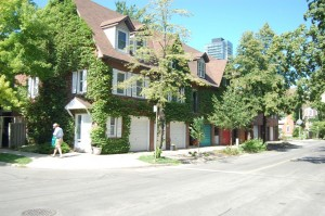 The faux-historic townhouses of the neighbourhood, built in 1980, have begun to look more authentically historic as the street trees mature and ivy climbs the outside walls. Author photo, June 2012.