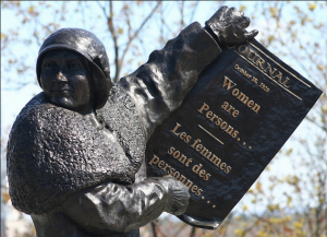 "Nellie McClung from the monument on Parliament Hill, showing historic newspaper headlines from the Persons Case. Photo: ""Les Girls"" – The Famous Five 10 by Douglas Sprott, CC BY NC 2.0."