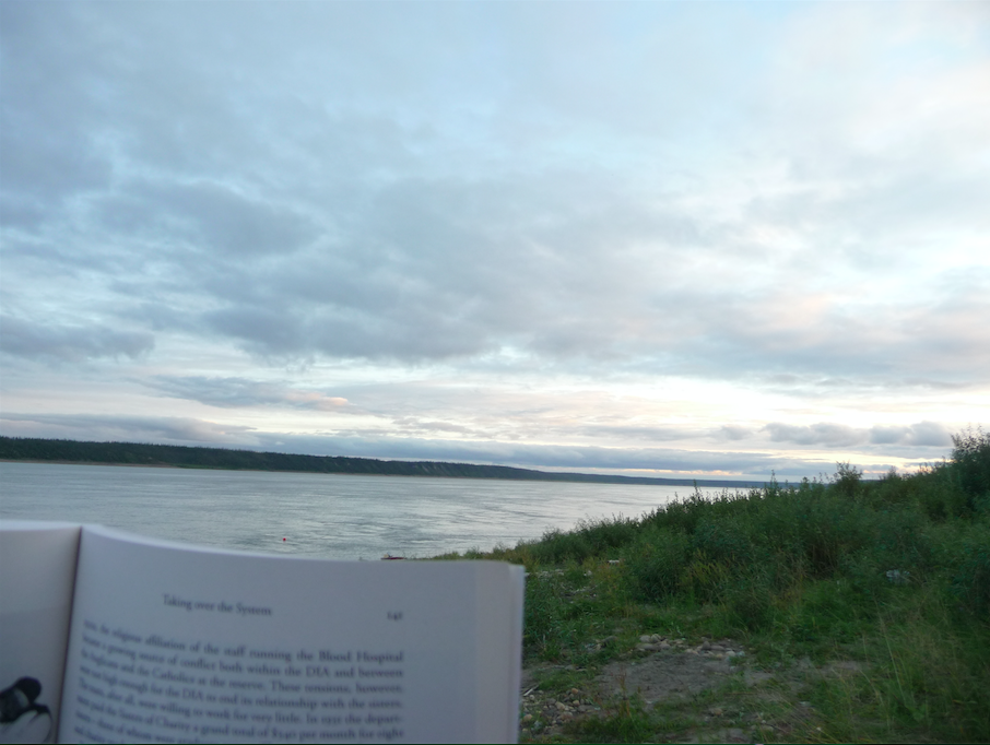 Reading for PhD Comprehensive Exams at Diighe'tr'aajil, Northwest Territories, with the Nagwichoonjik in the background. Photo Credit: Crystal Fraser.