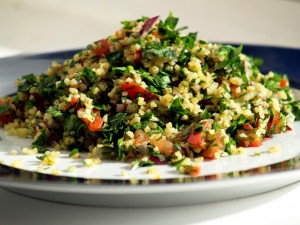 Tabbouleh is a Mezzeh (appetizer) made of cracked wheat with parsley, tomato, lemon, cucumbers, onion, and olive oil. Variations exist throughout the Levant