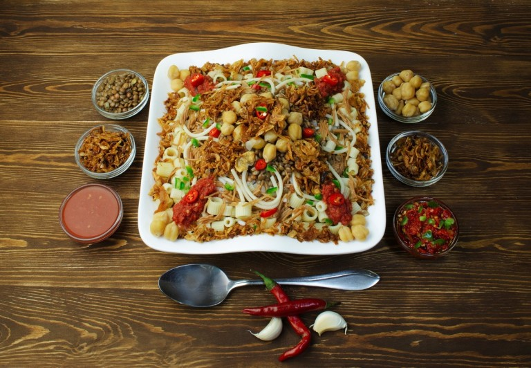 Kushari is made of rice, macaroni, and lentils mixed together, topped with tomato-vinegar sauce, garnished with chickpeas and crispy fried onions and sprinkled with garlic juice and hot sauce