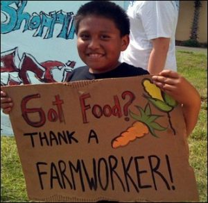 A young boy holding a Thank A Farmworker Sign made on cardboard.