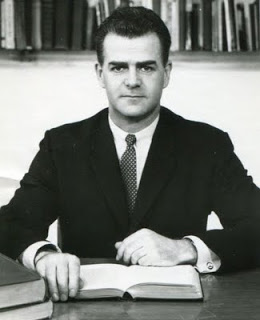 Frank Howard in a suit sitting at a desk