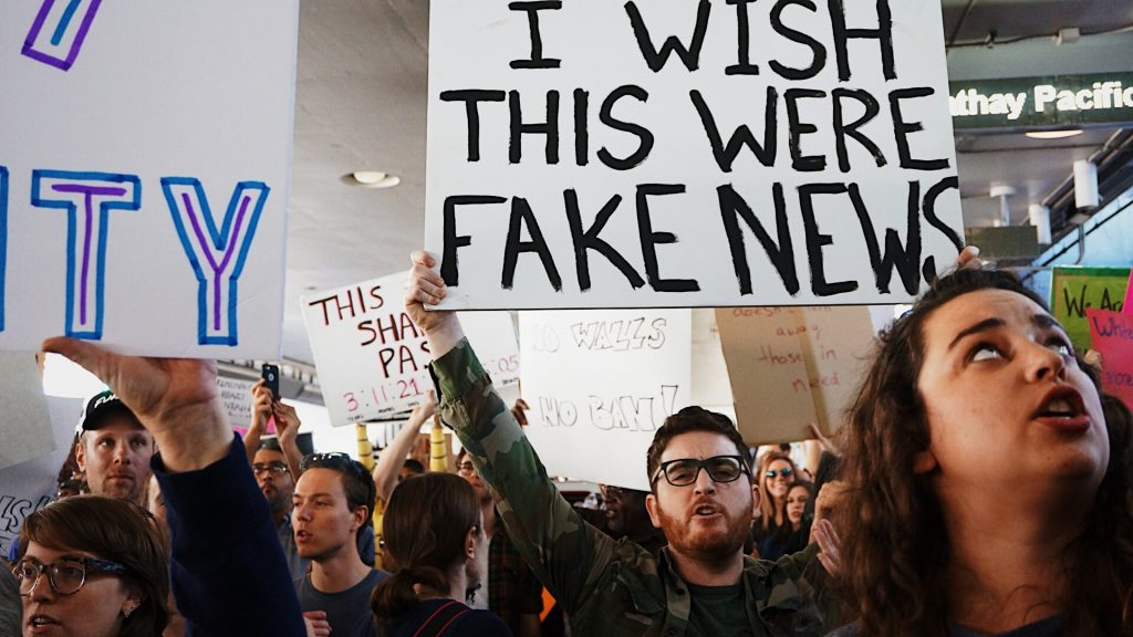 """Protest group with man holding a """"I Wish This Were Fake News"""" sign."""
