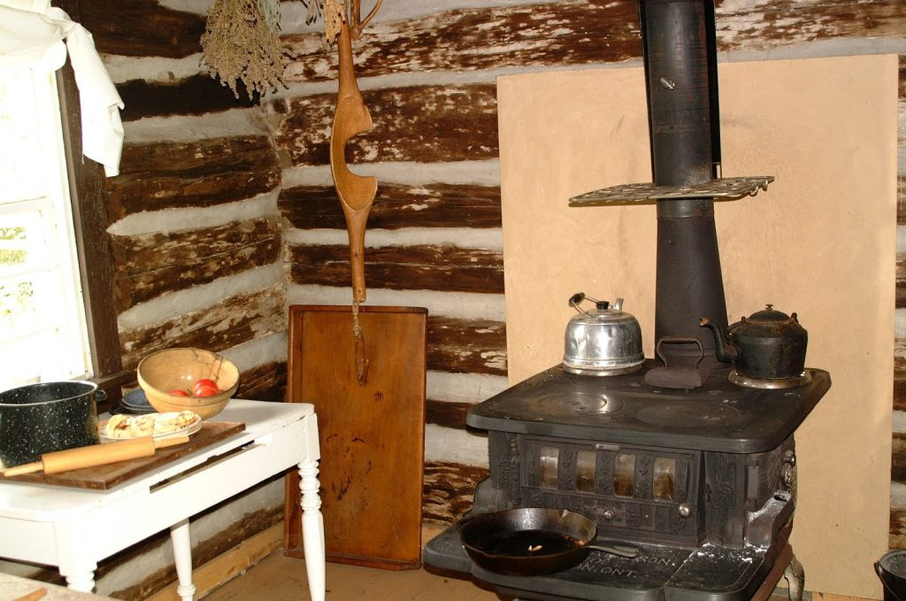 Stove, side table, and pots in a pioneer cabin.