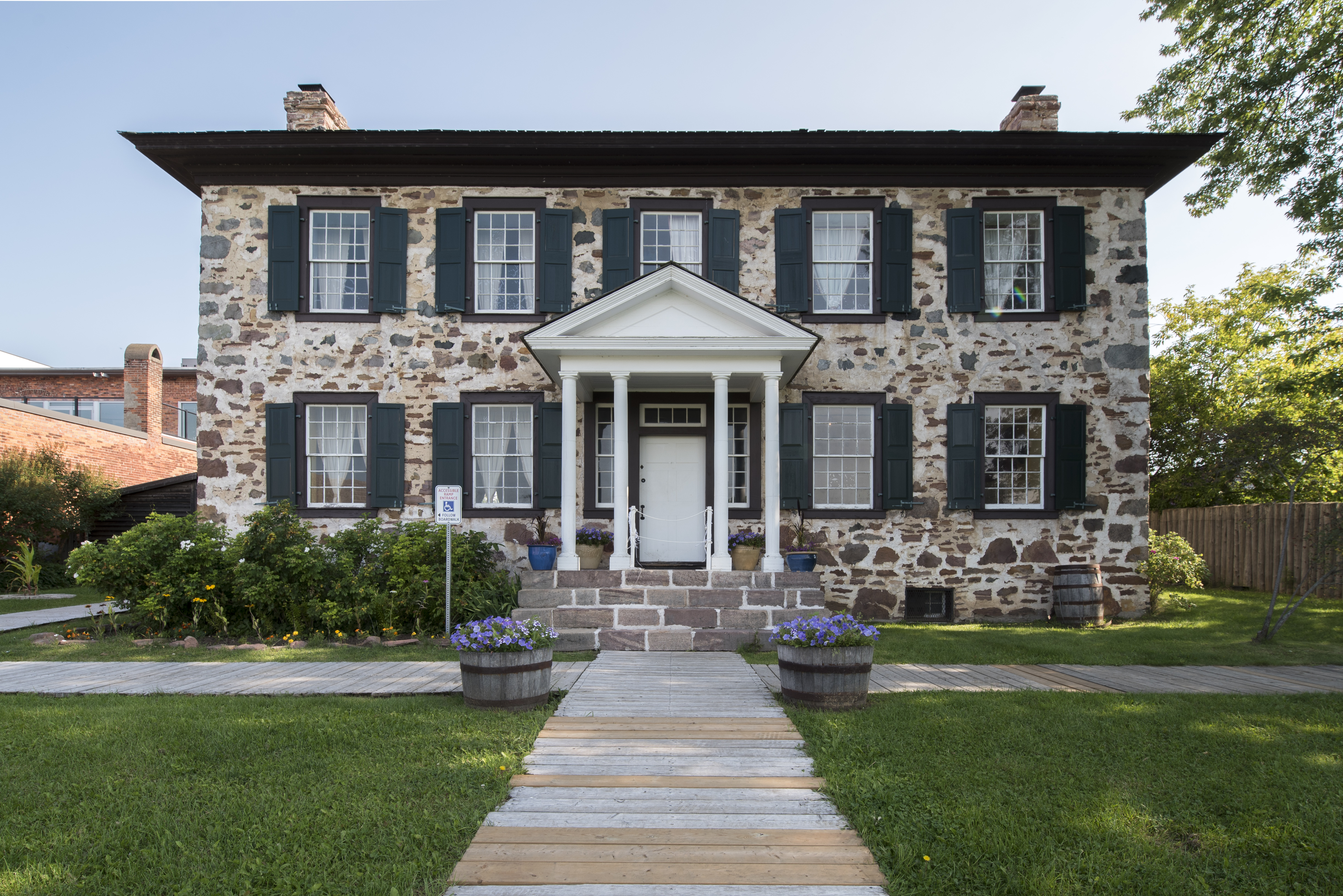 Two story stone building with walking and lawn in front.