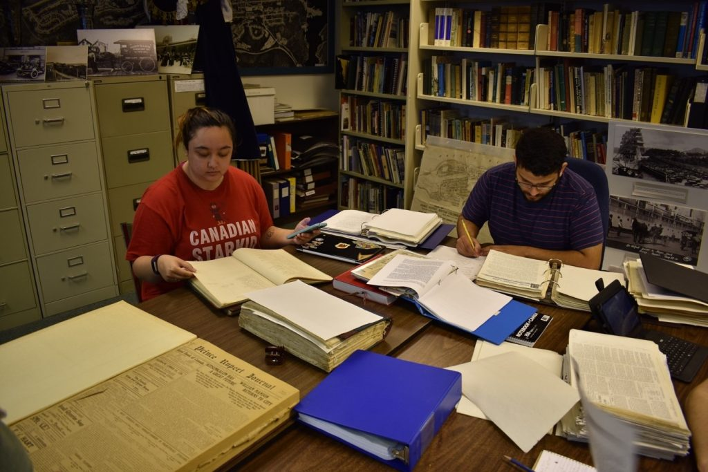 Two students working in an archives reading room with books piled on a desk
