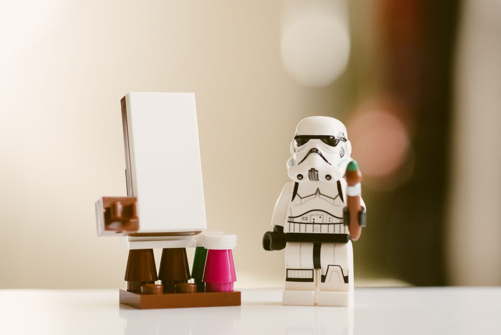 Lego storm trooper holding a paintbrush next to an easel.