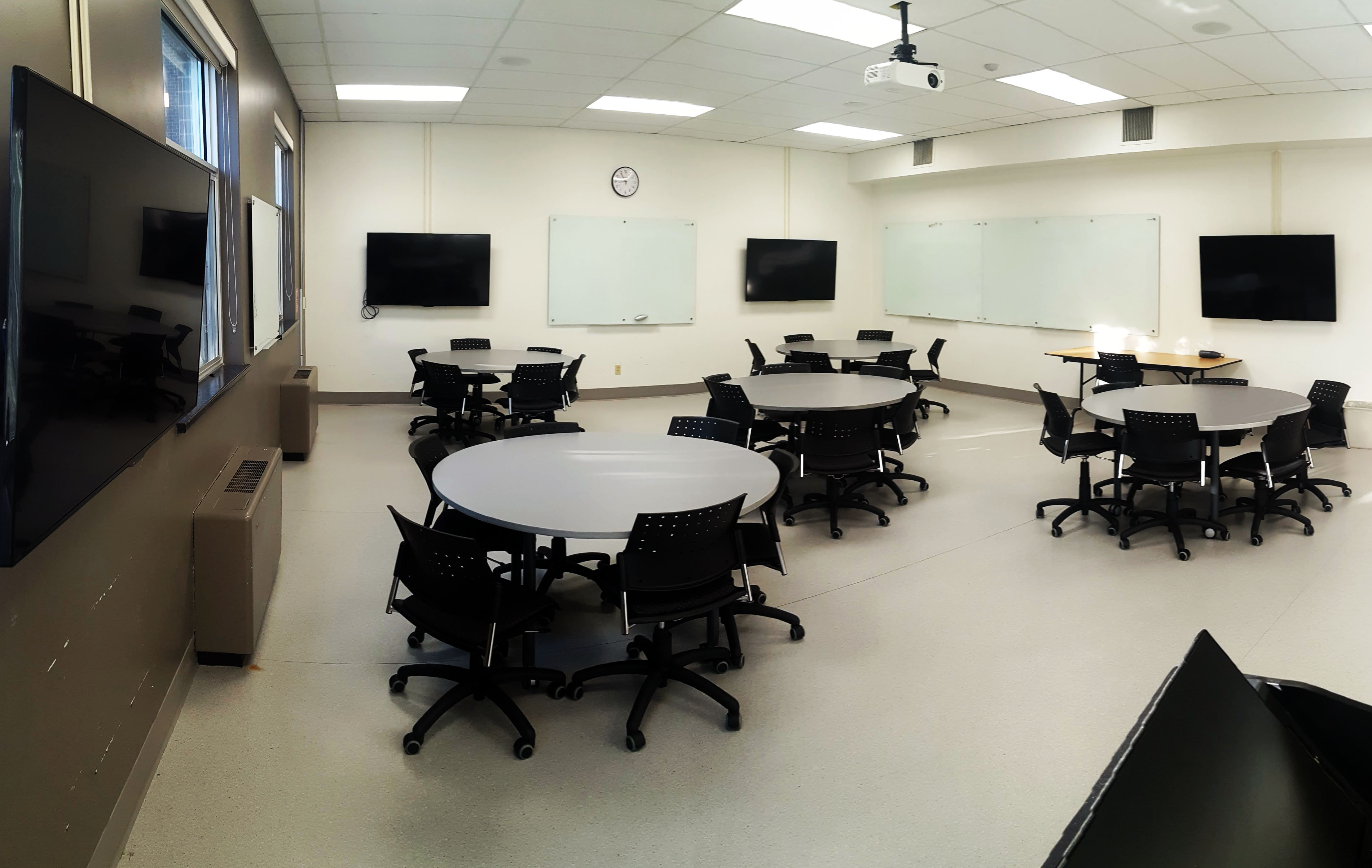 Room with tables and audio visual screens