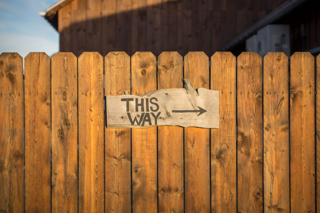 Fence with a sign saying 'This Way' with an arrow