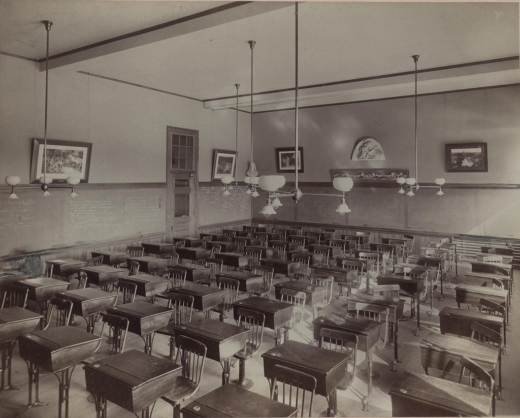 Black and white classroom filled with wooden desks.