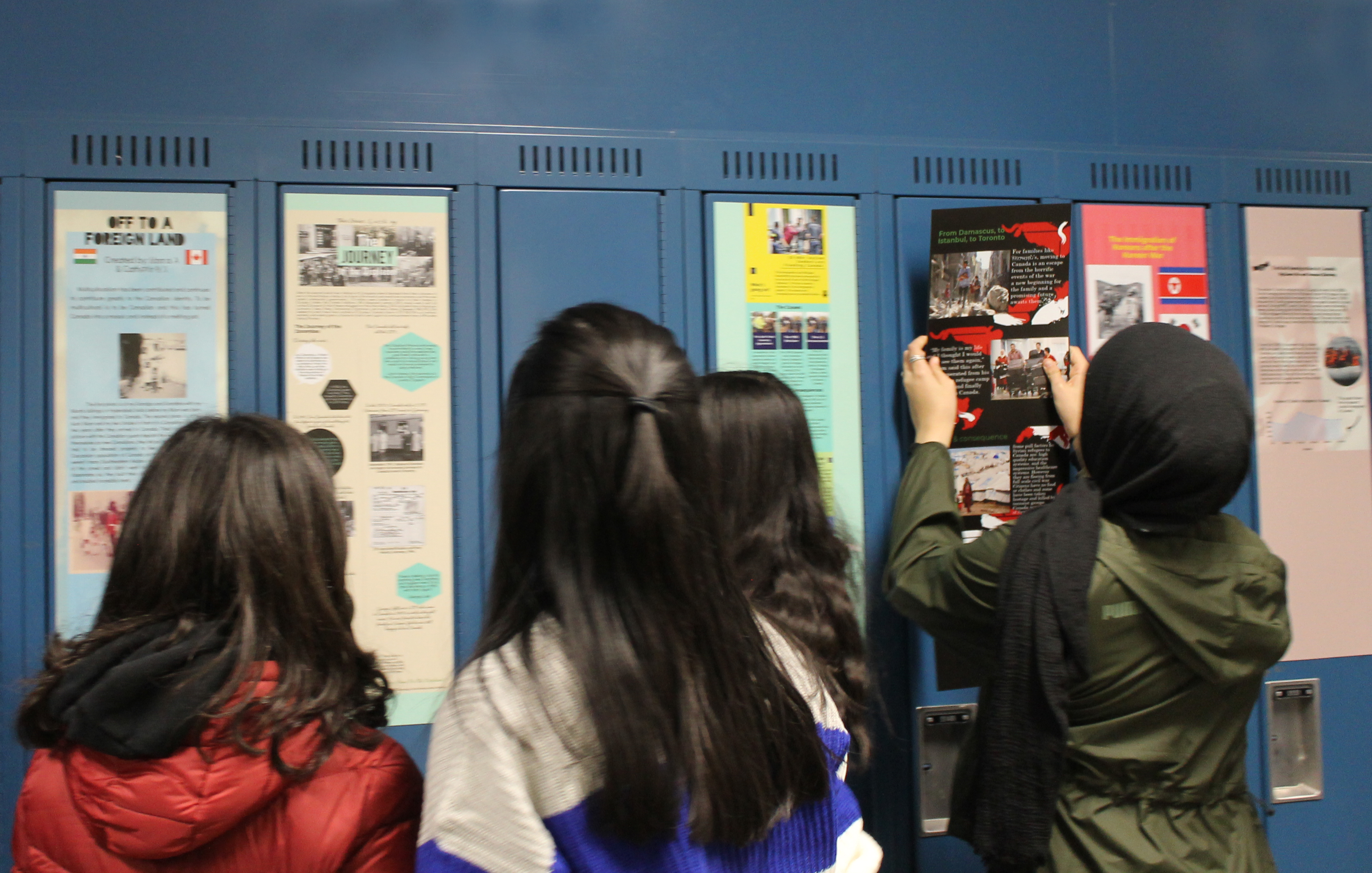 Four students hanging items on blue lockers.