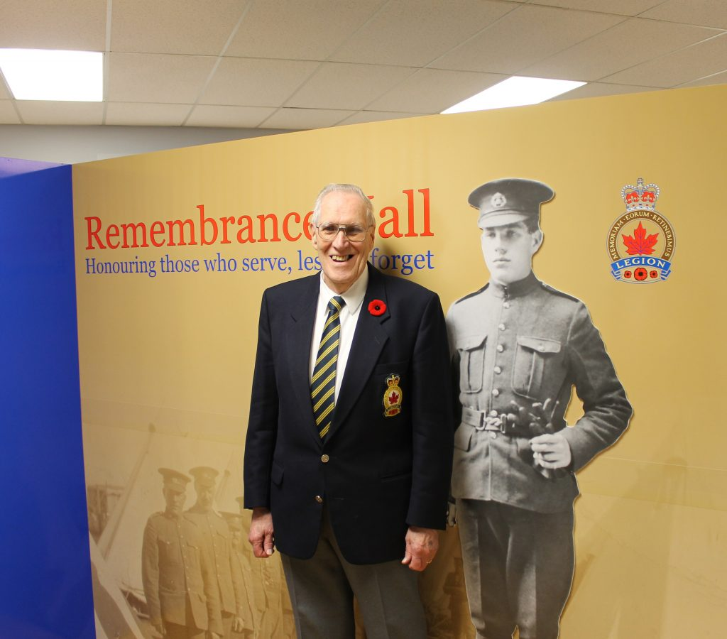 Man standing in front of Remembrance Hall sign