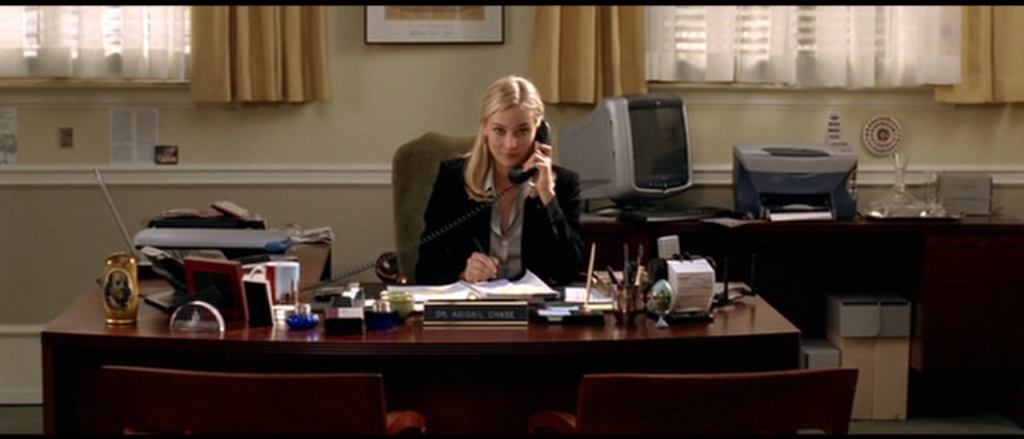 Dr Gates sitting at her large desk in her large office. She is speaking on the telephone.
