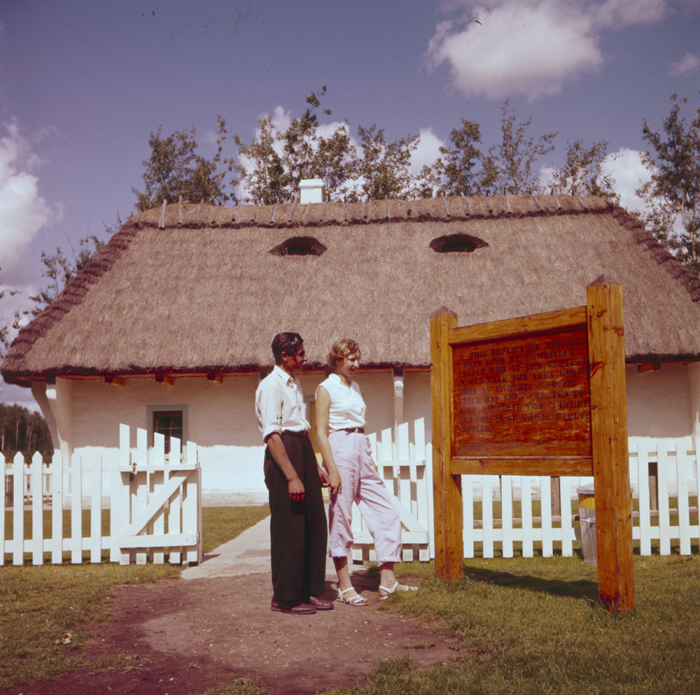 Two people reading a sign outside of a house museum
