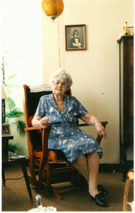 Elderly woman in a blue dress sitting in a rocking chair