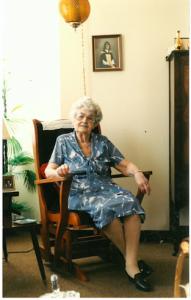 Elderly woman in a blue dress sitting in a rocking chair