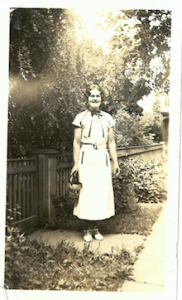 Photograph of a woman wearing a dress standing in a garden