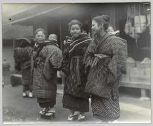 Three women standing on a street carrying children on their back