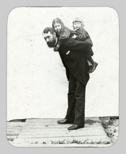 A man with two small children on his back.