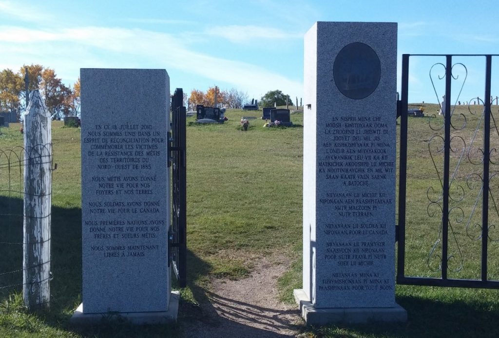 Two rectangular stone blocks frame the entrance to a cemetery. Both blocks have text inscribed on them. The shorter one on the viewer's left has French text, while the one on the right has Michif text.