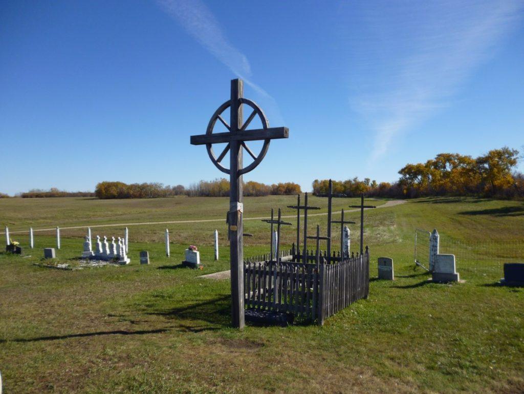 A mass grave sits at the edge of a cemetery. It consists of a single large wooden cross with nine smaller wooden crosses standing behind it. The nine smaller crosses are surrounded by a short wooden fence.
