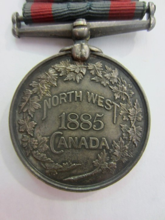 "An image of a medal inscribed with the words ""North West 1885 Canada."" The edges of the medal are inscribed with a depiction of a maple leaf wreath."