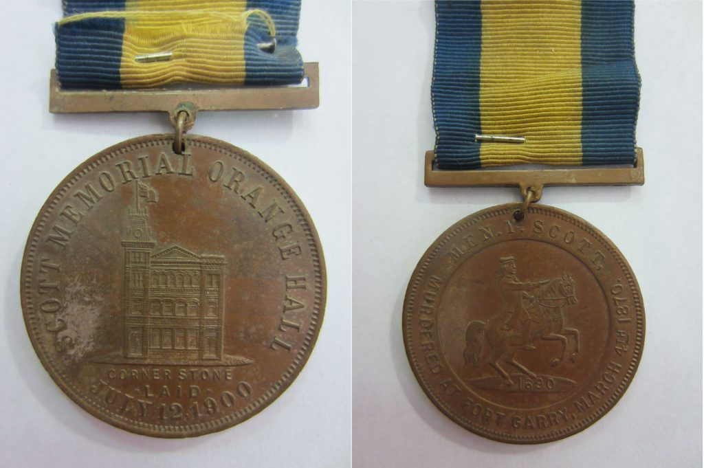 "Two sides of a medal. One side is engraved with an image of a building and the words ""Thomas Scott Memorial Hall"", the other with the image of a man on a horse and the words ""Men.Y.Scott, Murdered at Fort Garry, 4 March, 1870."""