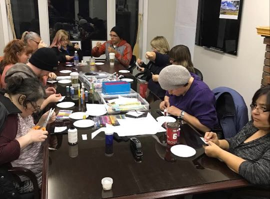 Group of people beading around a table