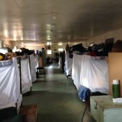 Photo of bunkhouse accomodations for temporary workers for a canning plant near Chatham, Ontario. Shows overcrowding and dim space.