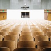 A lecture hall with wooden chairs