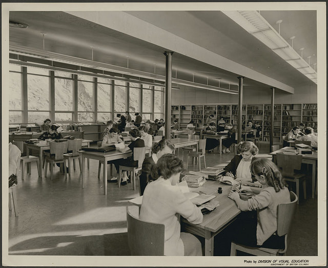 Students sitting at tables in a library.
