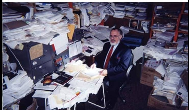 Man at desk surrounded by papers